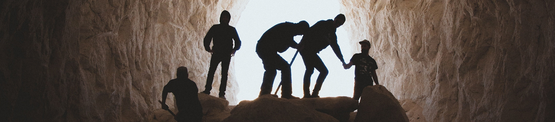 A group of men digging inside of a cave