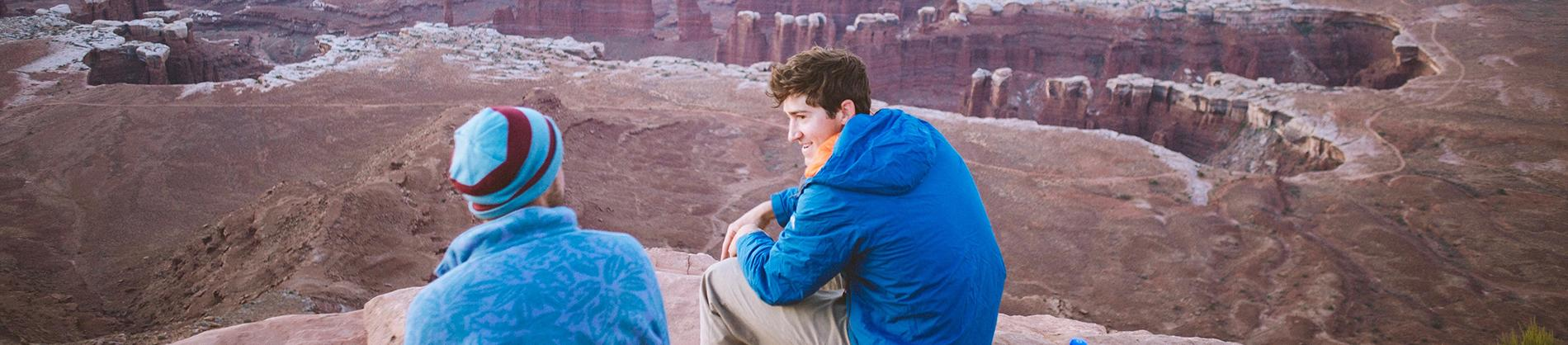 Two men sat on top of a mountain talking