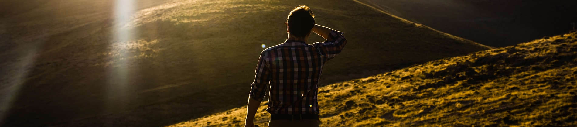 A man looking towards a sunset over a hill