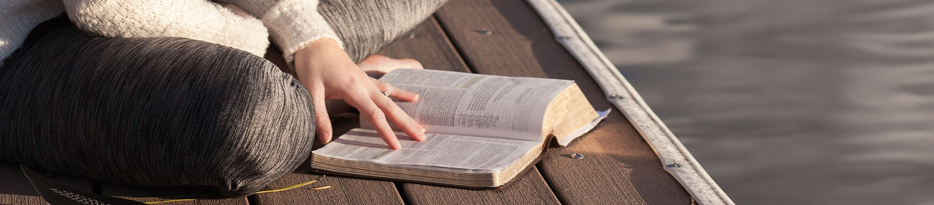 A women sat on a dock reading her bible