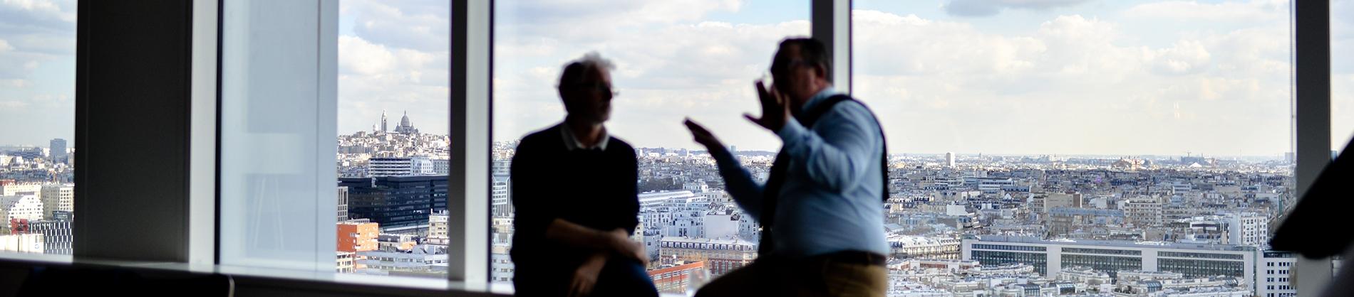 Two men sat on a windowsill talking