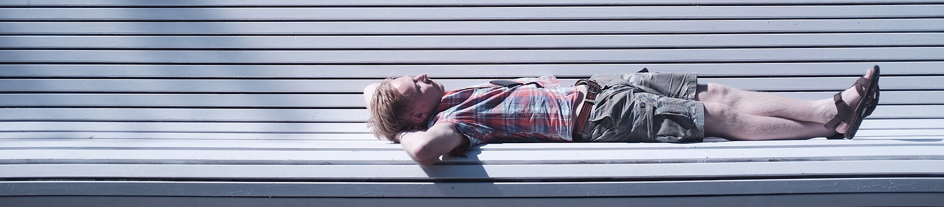 A man lying on a white bench looking up at the sky