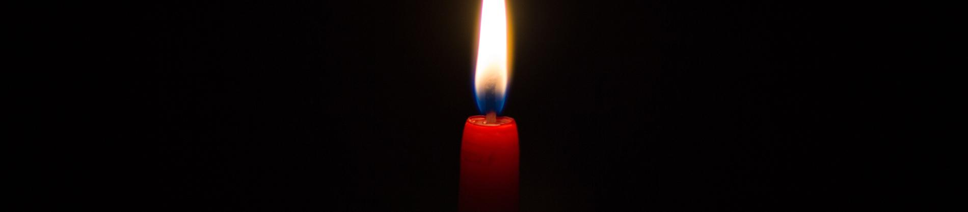One lit red candle in a dark room