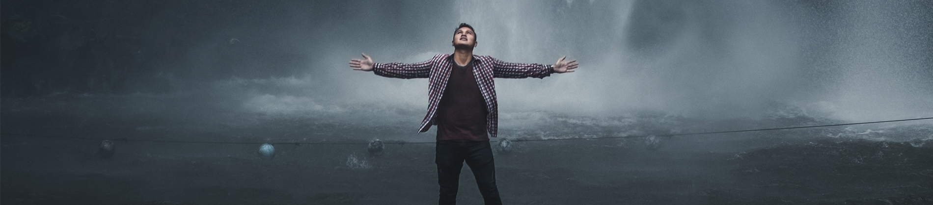 A man in a checked shirt with his arms wide in front of a cloudy landscape