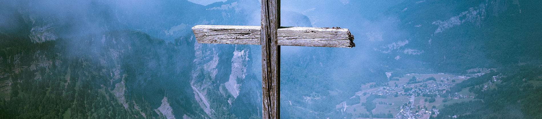 Wooden cross with a mountain range behind