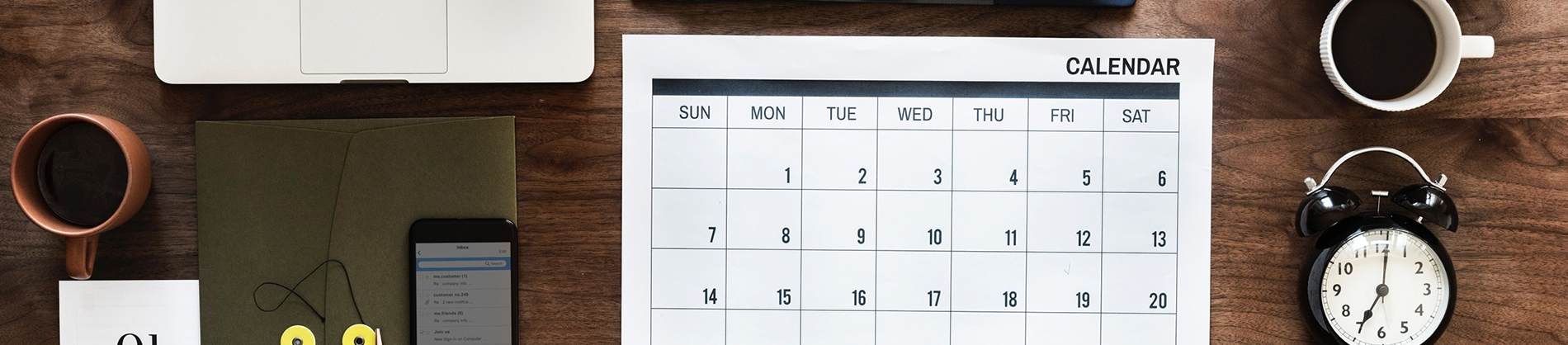 A wooden desk with a calendar, clock and phone on