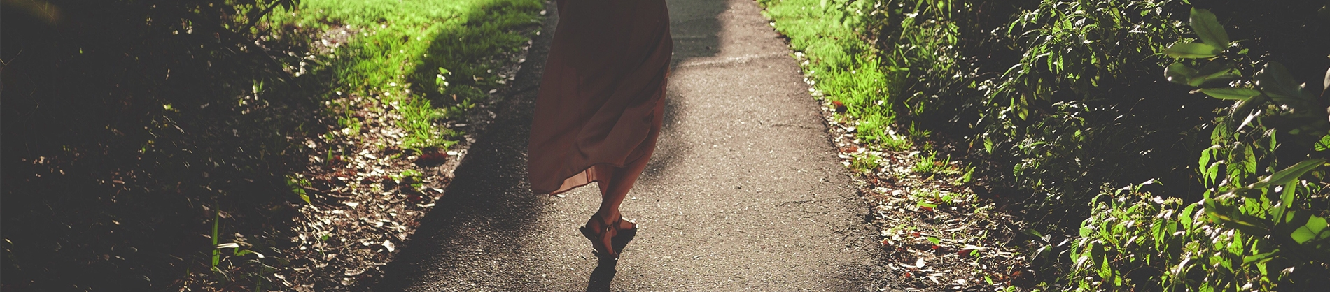 A women walking down a path with grass either side