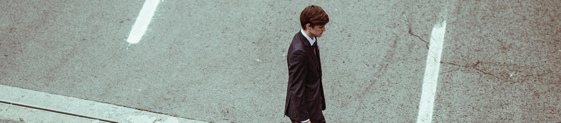 A man dressed in a suit walking across the street