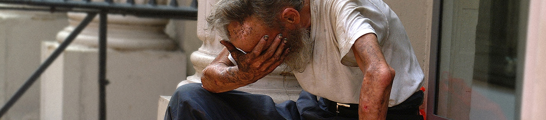 A older man sat on some steps with his head in his hand covered in dirt