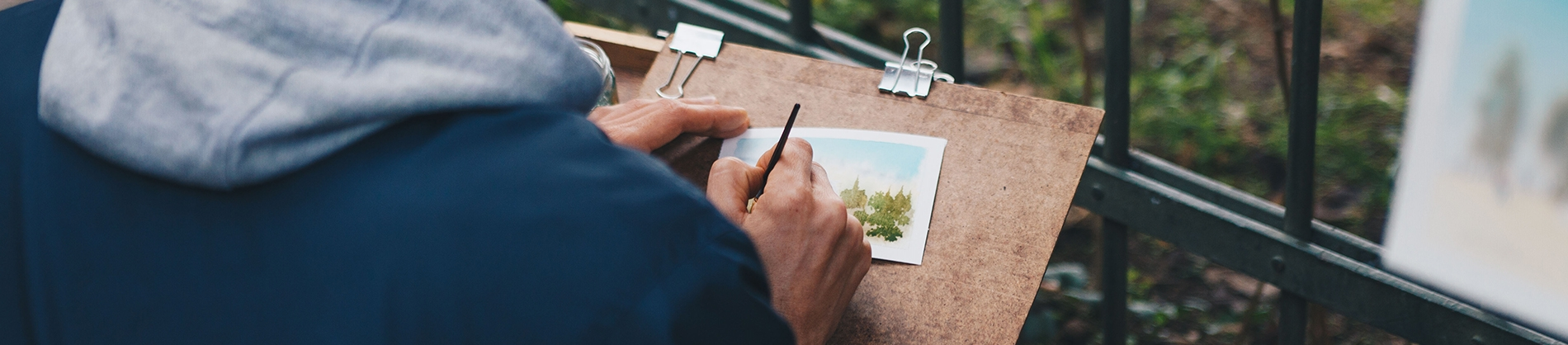 A man painting onto a small piece of paper