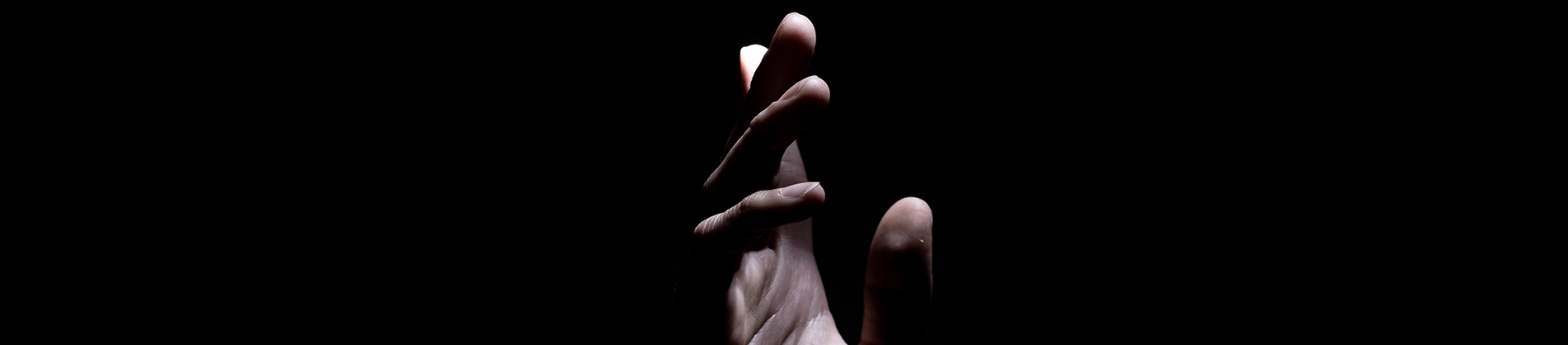 A black background with a hand reaching into the light