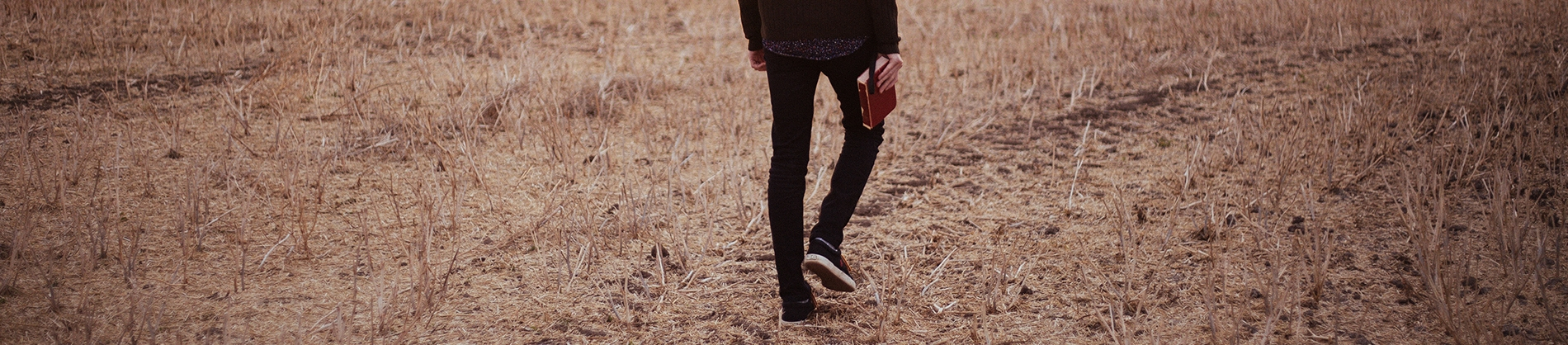A man walking through a dry field carrying his bible