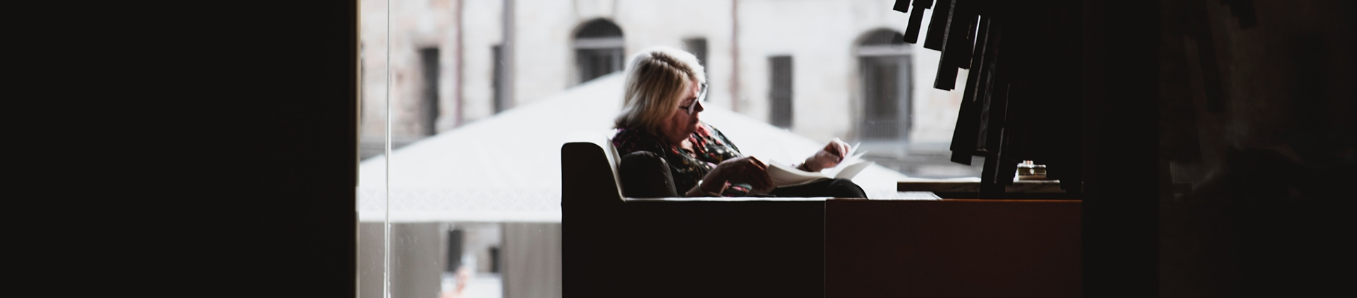 A women sat on a chair next to a window reading