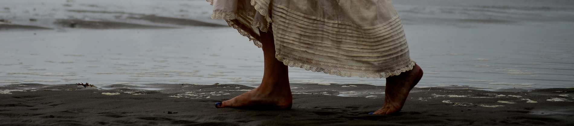 A women bare foot walking across sand in a creme dress