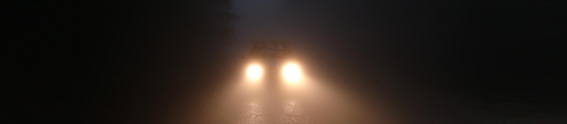 Car headlights on a dark road