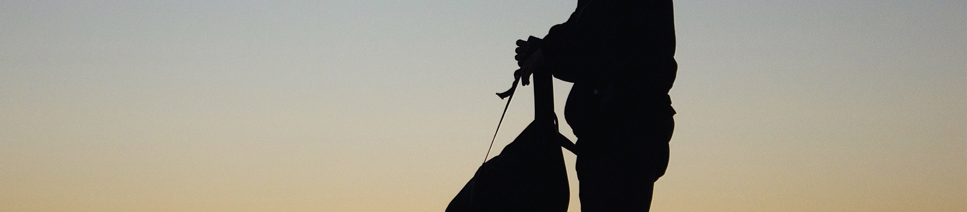 A silhouette of a man holding a backpack