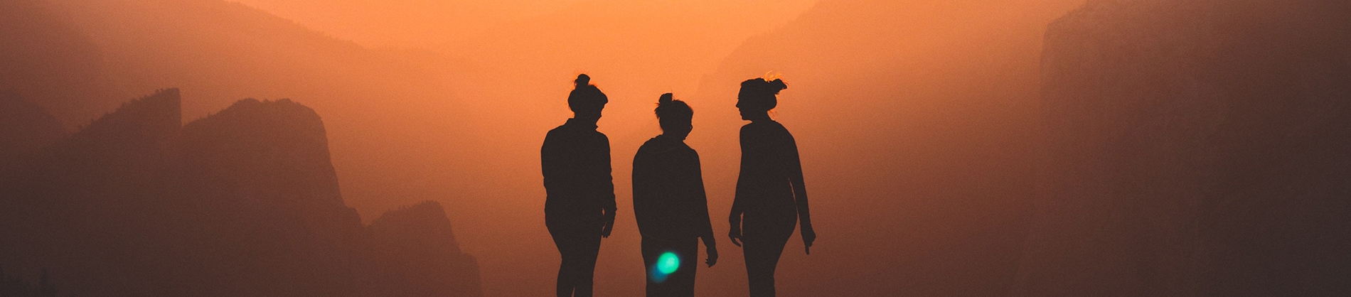 Silhouette of three friends with the sun setting behind them