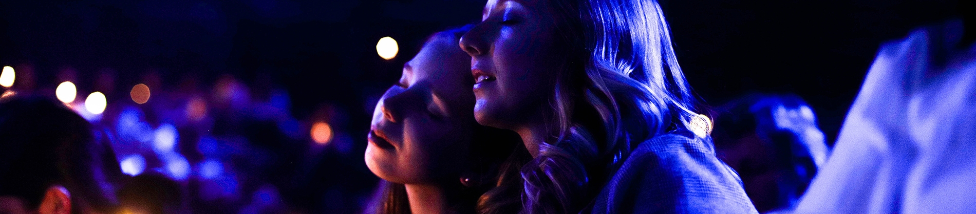 Two women with their eyes closed in worship