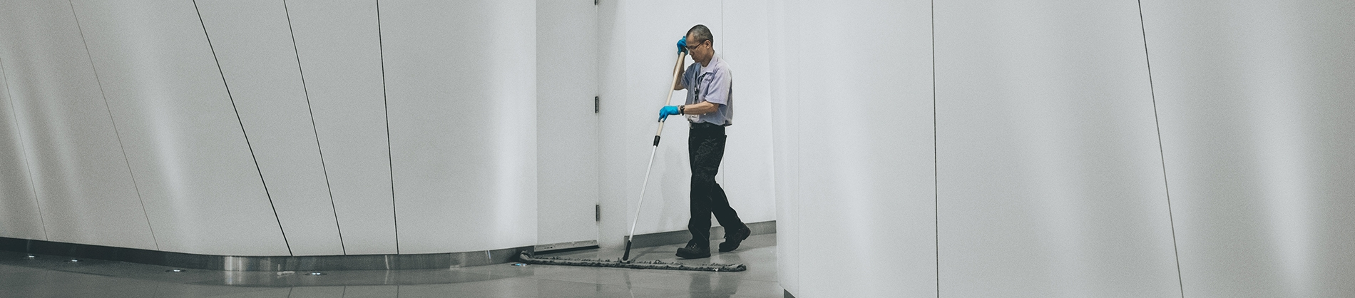 A cleaner mopping the floor of a office building