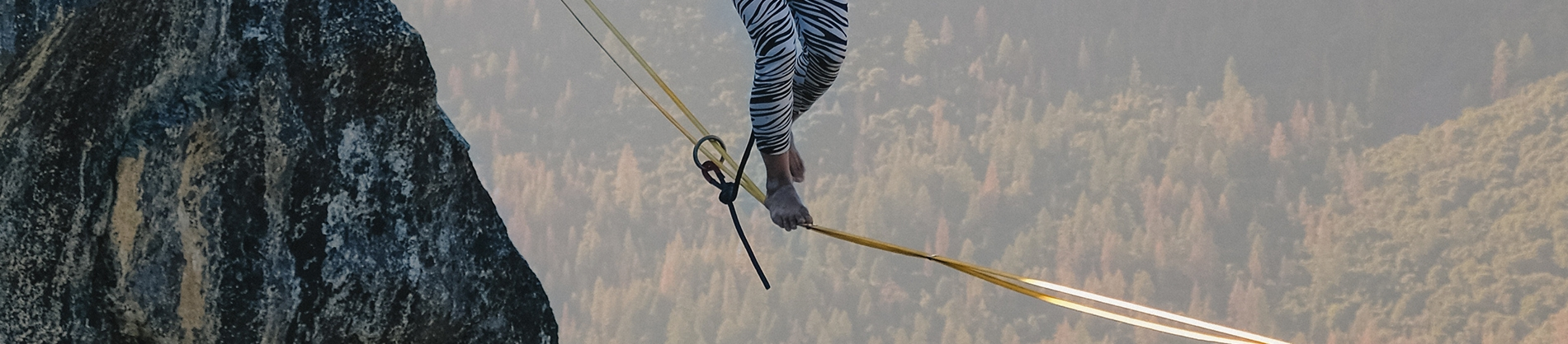 A person walking on a tightrope over a valley