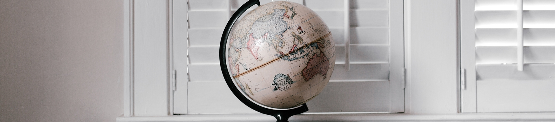 A globe sat on a shelf with white shutters behind