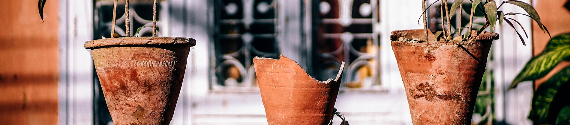 Two clay plant pots with one smashed plant pot