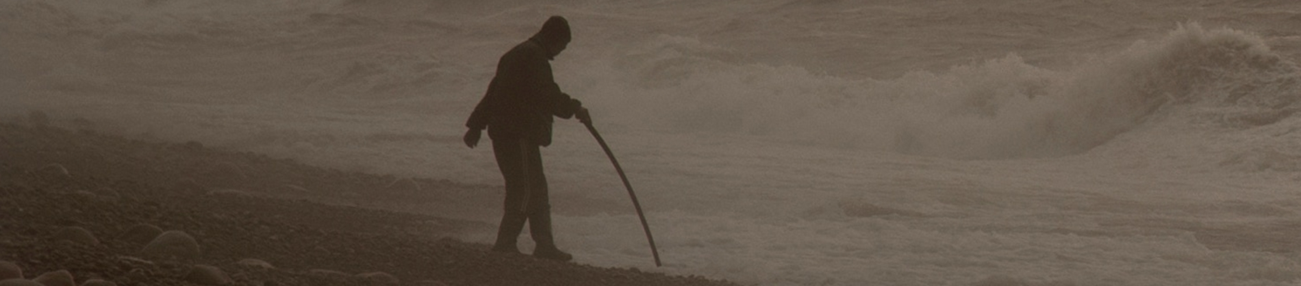 A man walking towards the ocean with a walking stick