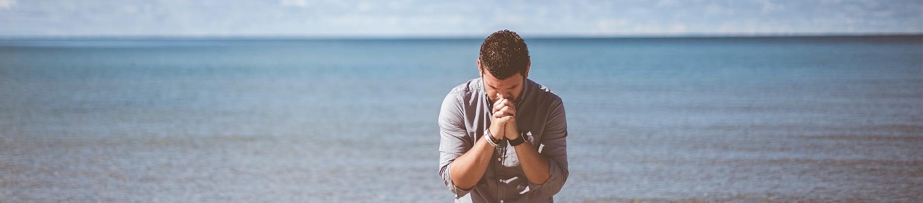 A man kneeling on a beach in prayer