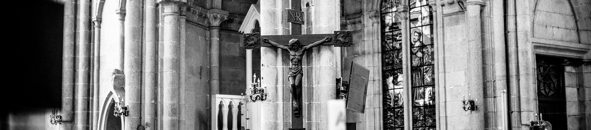 Black and white photo of a church with a statue of Jesus on the cross on the wall