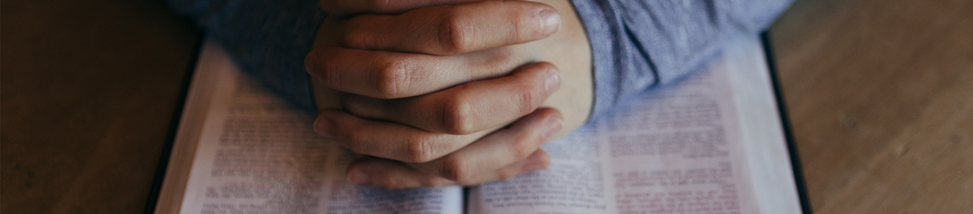 Praying hands on top of a bible