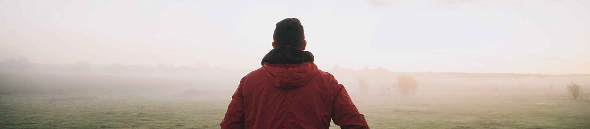 A man in a red jacket walking into a foggy field