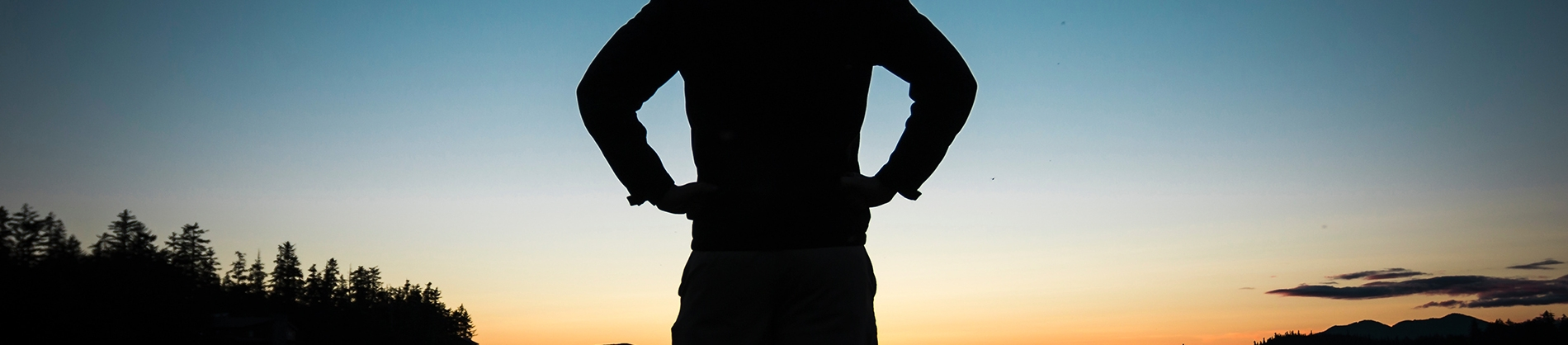A silhouette of a man stood in front of a sunrise