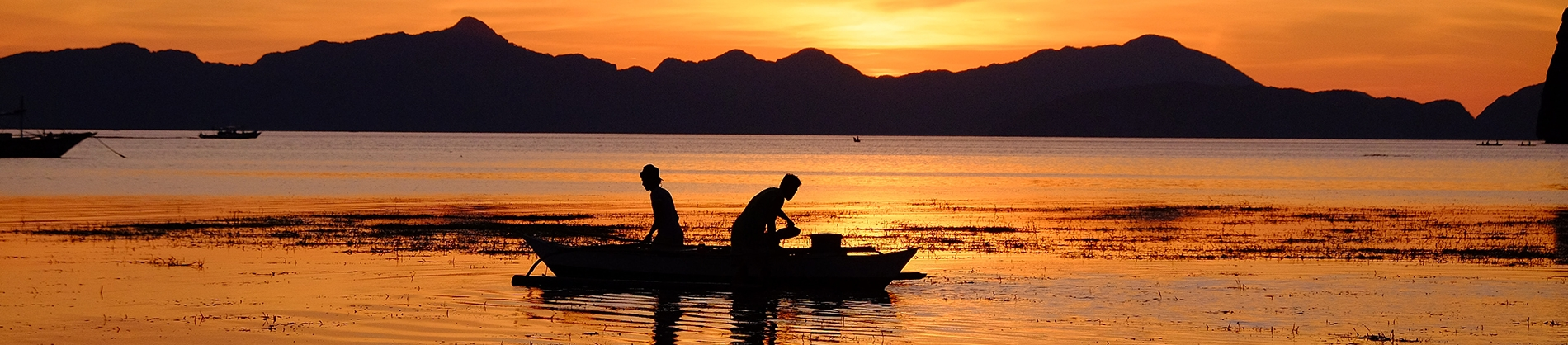 Two fishermen out on a boat at sunrise