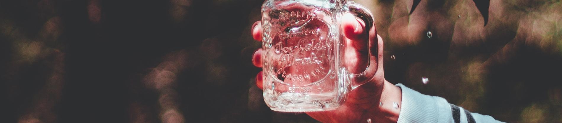 Someone holding up a glass mason jar