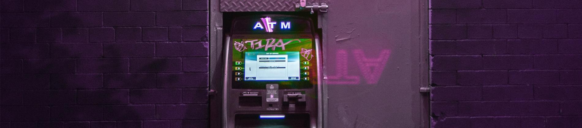 ATM machine against a purple wall