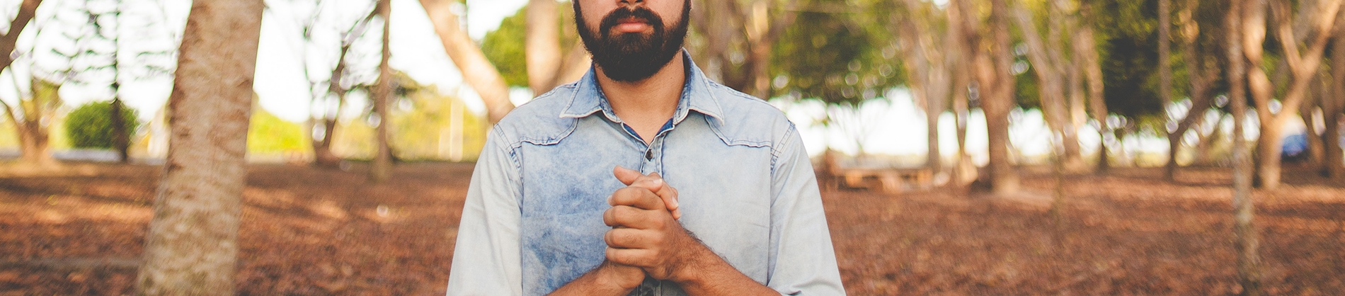 A man stood in a forest with his hand together in prayer