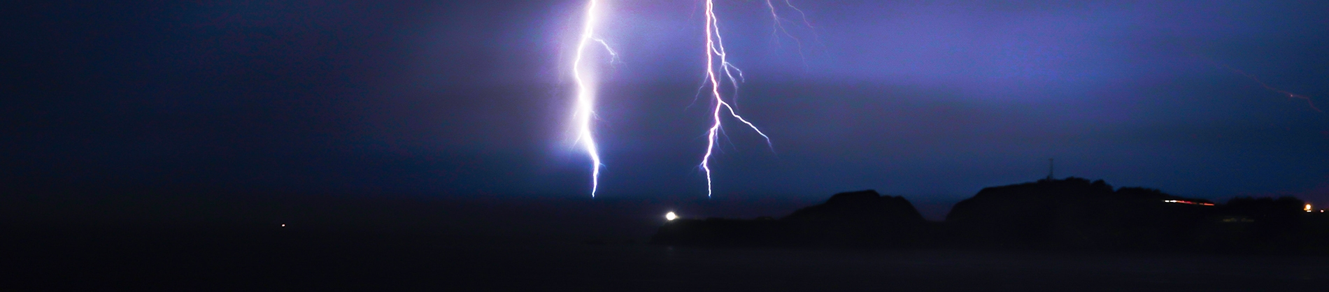 Lightening bolts flashing down on a dark landscape