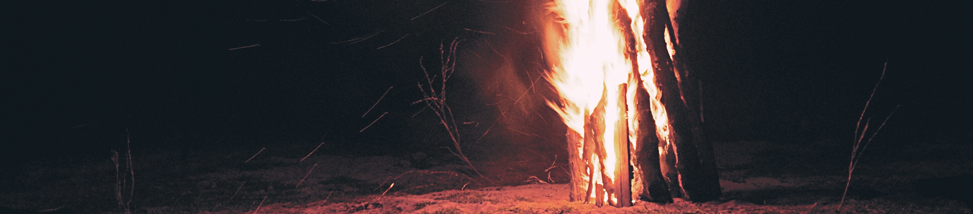 A pile of wood on fire on a beach