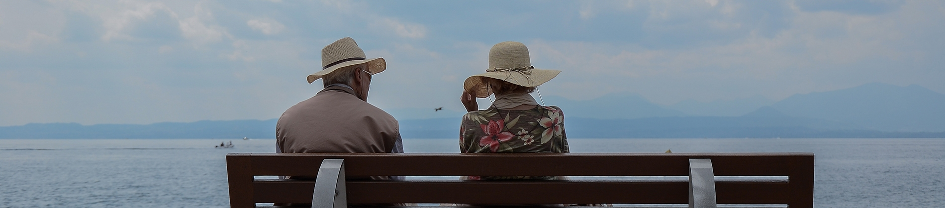 A elderly couple sat on a bench looking out to sea