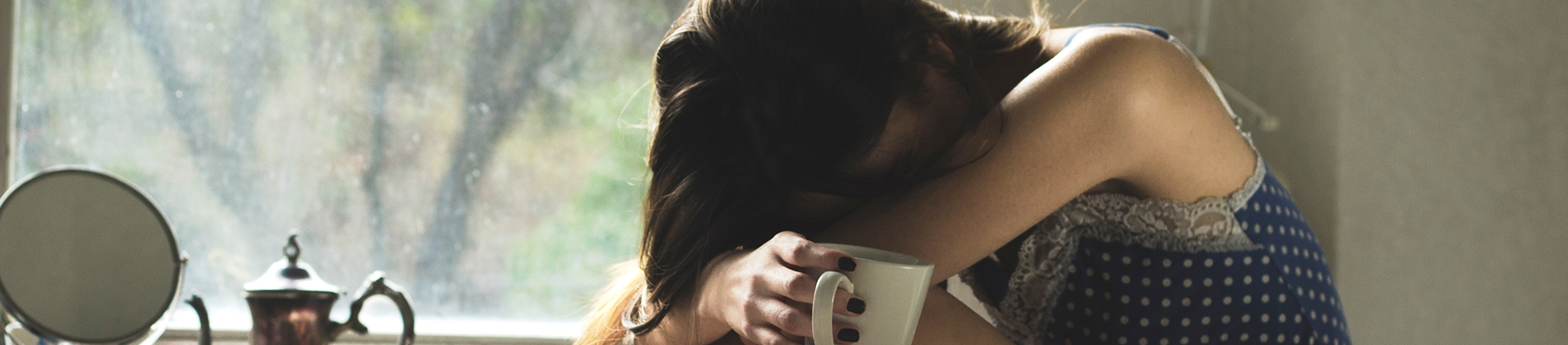 A women crying into her lap holding a mug