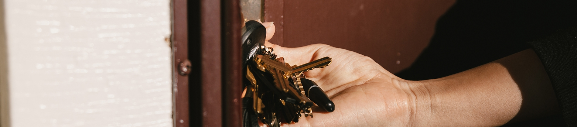 A women putting her keys in to a front door
