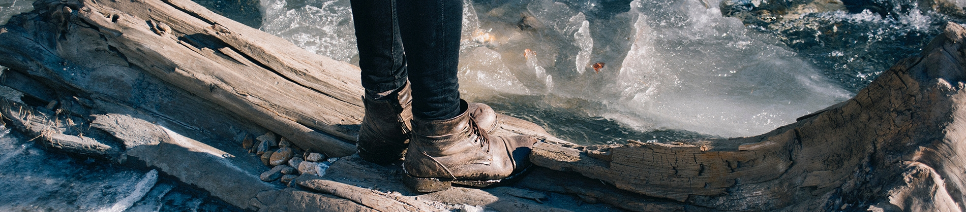 A girl in brown boots stood on a large piece of wood in the water
