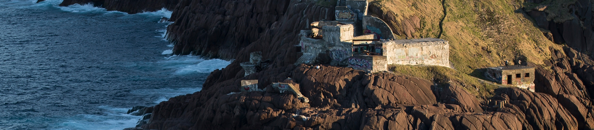Houses set on a rocky cliff down to the sea