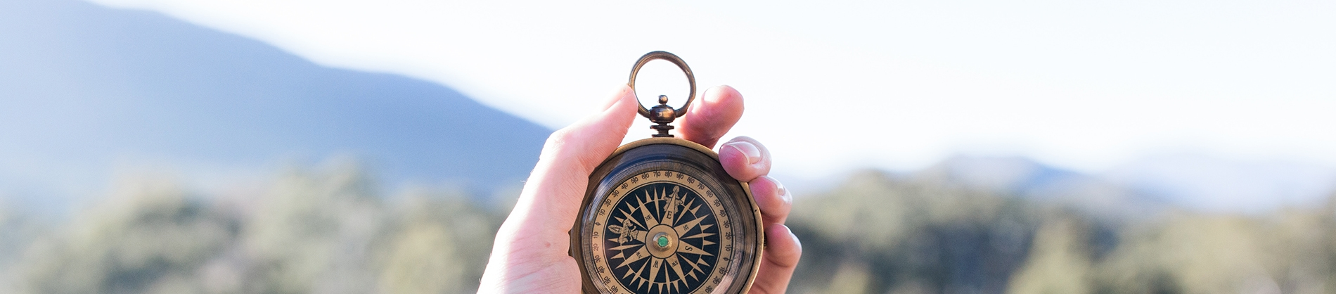 A hand holding a compass up with a landscape behind