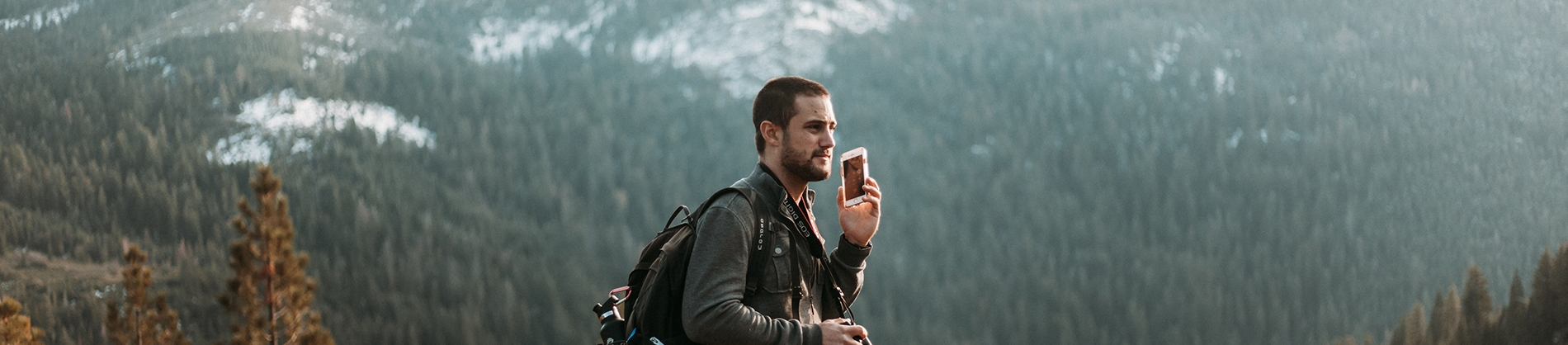 A guy high up on a mountain speaking on the phone