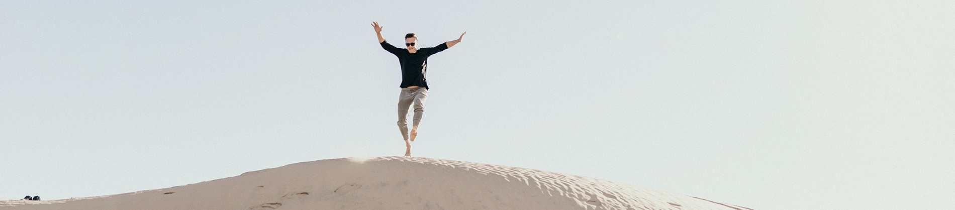 A man jumping down a sand dune with his hands in the air