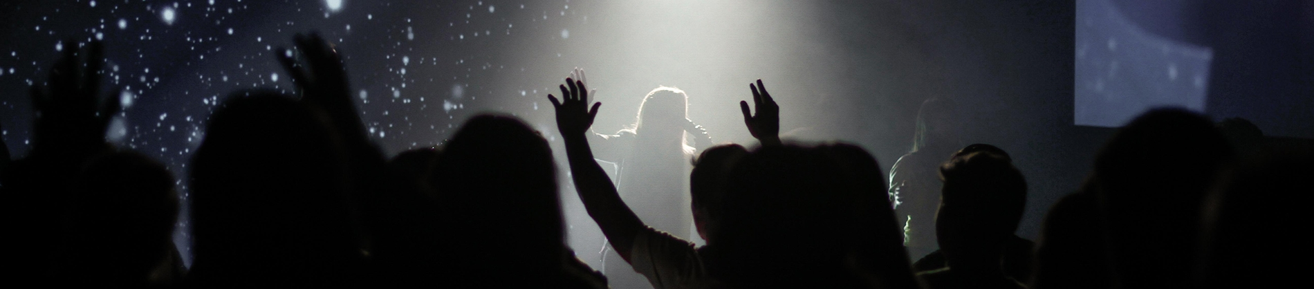 A women leading worship, congregation with their hands in the air