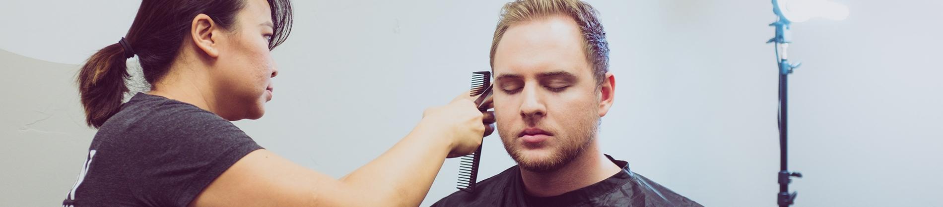 A women cutting a man's hair in a barbers shop