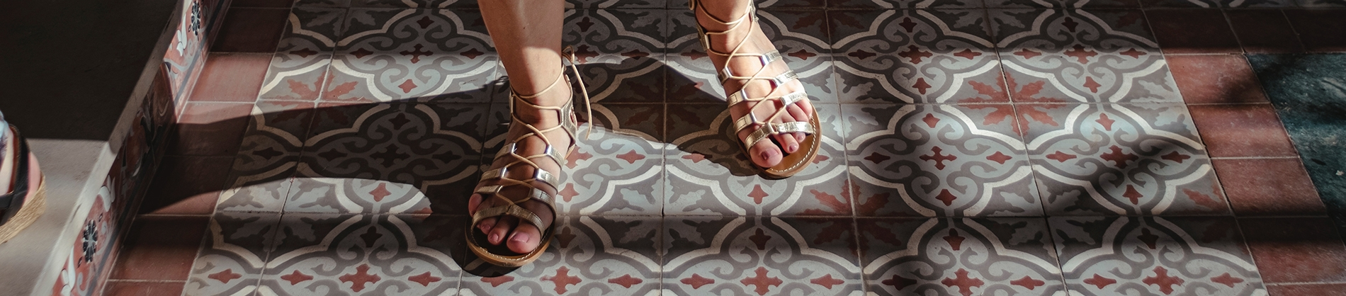 A women in sandals walking on a ornate tiled floor