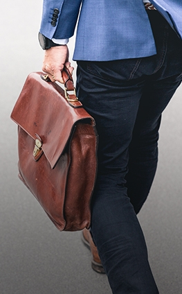A man in a suit with a brown briefcase